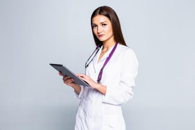 セーターの若い女性の笑顔、タブレットpcコンピューターを使用してスカーフ、灰色の壁に分離されたビデオ通話を行います。健康的なライフスタイル、オンライン治療コンサルティング、寒い季節のコンセプト。 無料写真