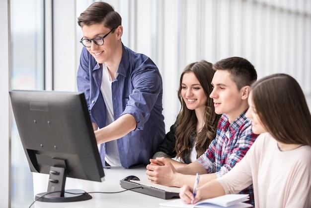 大学でコンピューターのpcを見て笑顔の学生。 Premium写真