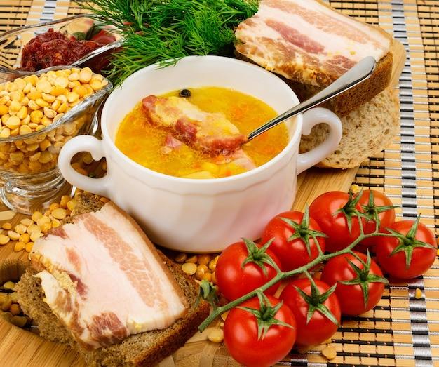 Суп гороховый с беконом. в белой керамической чашке. украшается укропом и помидорами черри. Premium Фотографии