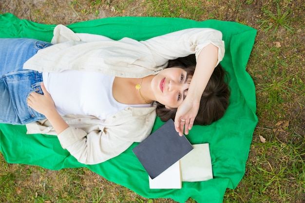 Peaceful carefree college girl happy to finish study book Free Photo