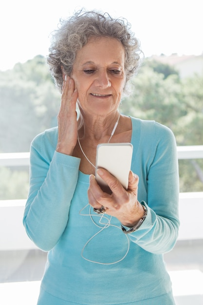 Peaceful focused senior lady setting playlist Free Photo