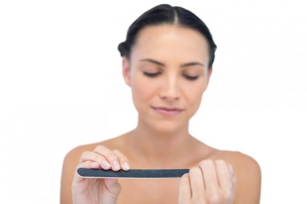 Peaceful natural young model using nail file Premium Photo