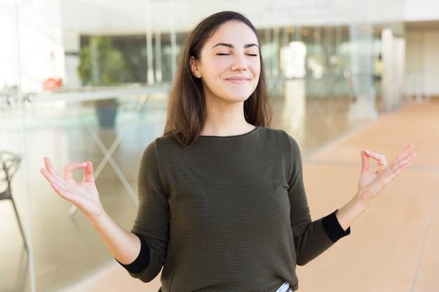 Bella donna sorridente pacifica che fa gesto di zen Foto Gratuite