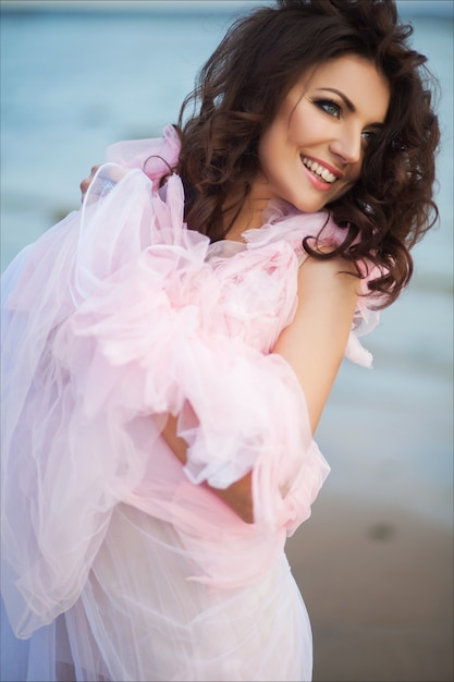 Peaceful vacation paradise woman walking on sunset ocean beach. smiling excited girl in pink romantic dress Premium Photo