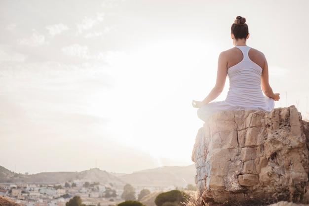 Мирная женщина, медитирующая на закате Premium Фотографии