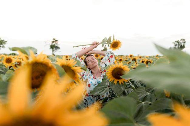 ひまわり畑でポーズをとって穏やかな女性 無料写真