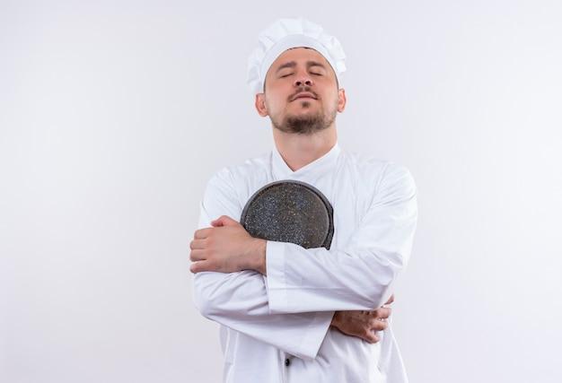 孤立した白いスペースに目を閉じてフライパンを保持しているシェフの制服を着た平和な若いハンサムな料理人 無料写真