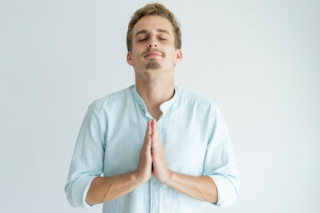 Peaceful young man praying with his eyes closed and keeping hands together. Free Photo