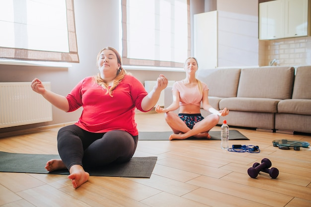 Peaceful young slim and plus size models in lotus pose and meditating Premium Photo