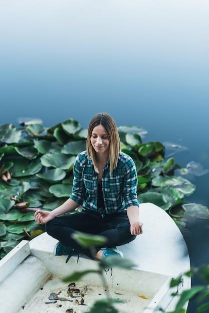 Мирная молодая женщина медитирует в позе лотоса на воде в окружении листьев кувшинки Premium Фотографии