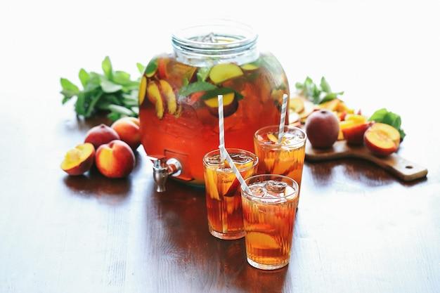 Персиковый сок в чашках и в большой банке с кусочками фруктов внутри Бесплатные Фотографии