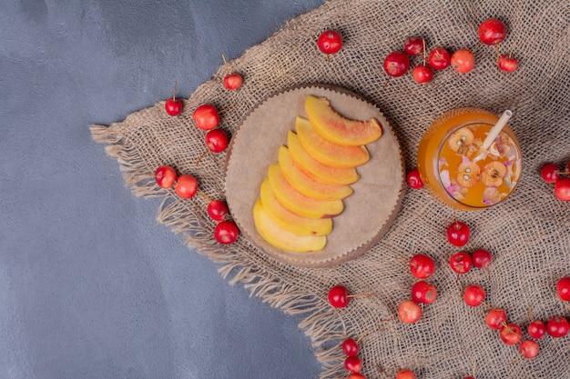 Ломтики персика, вишни и стакан фруктового сока на синем. Бесплатные Фотографии