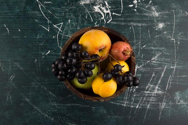 Персики и виноград в деревянной миске на черной доске в центре Бесплатные Фотографии