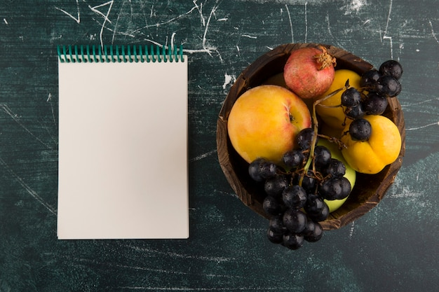 Персики и виноград в деревянной миске с записной книжкой в сторону Бесплатные Фотографии