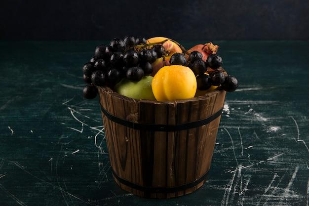 Персики и виноград в деревянном ведре на черной доске Бесплатные Фотографии