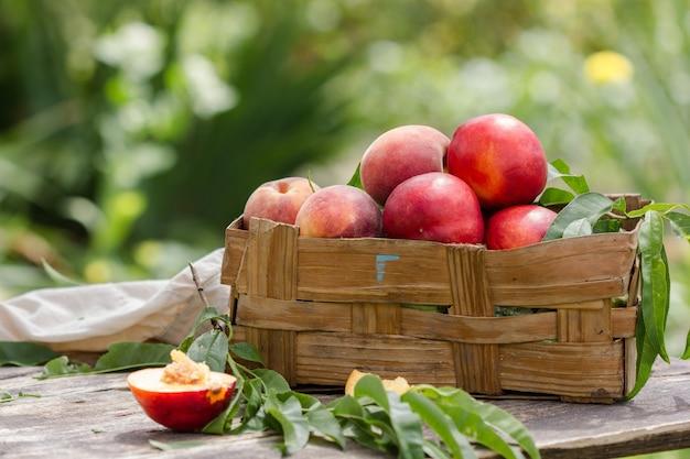 Персики с листьями в деревянном ящике на естественном саду Premium Фотографии