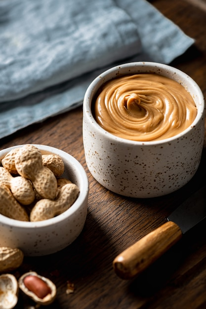 Peanut butter in a ceramic bowl on wooden background Premium Photo