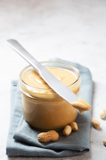 Peanut butter in a glass jar and knife on the table Premium Photo
