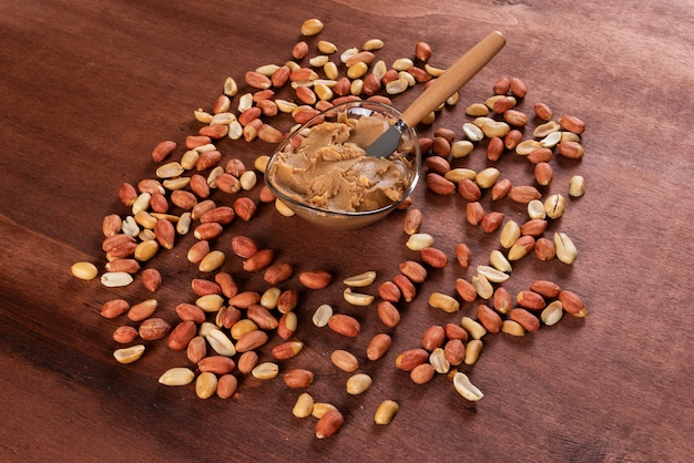 Peanut butter surrounded by peanuts on wooden horizontal Free Photo