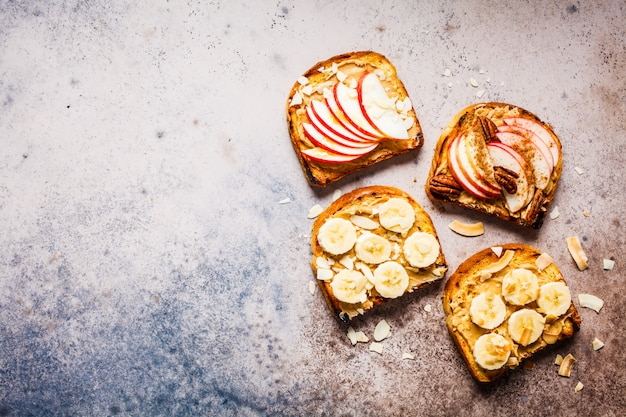 Peanut butter toasts with banana and apple on a gray background, flat lay. Premium Photo