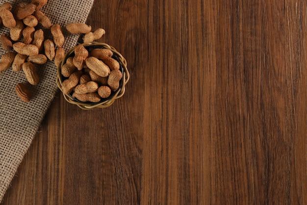油、ピーナッツバターを作るのに役立つピーナッツ組成物。健康的で食事の栄養に最適です。コンセプト:調味料、ドライフルーツ、食品。上面図。 Premium写真