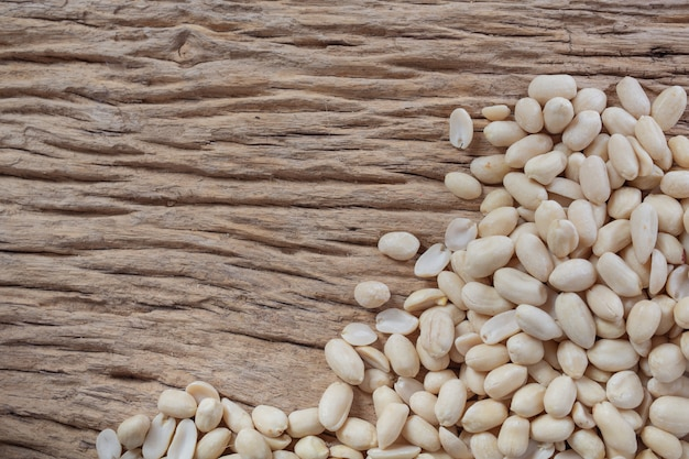 Peanut seeds on a wooden background in the kitchen Free Photo