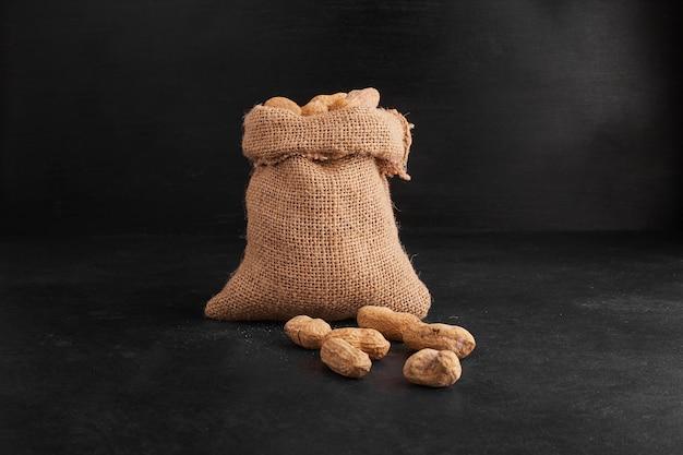 Gusci di arachidi da un pacco rustico su sfondo nero. Foto Gratuite