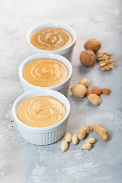 Peanut, walnut and almond butter on the gray table Premium Photo