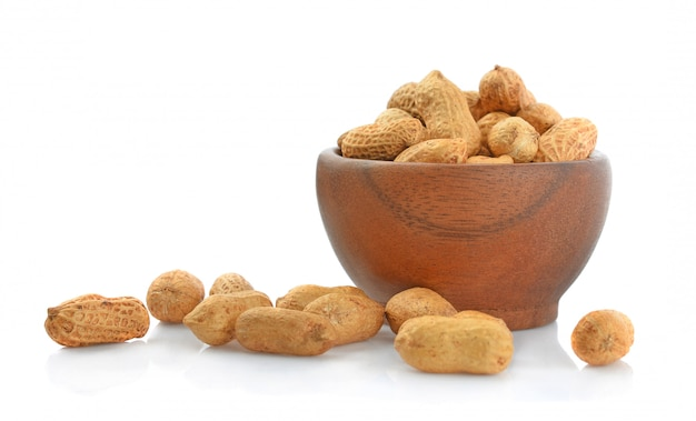 Peanut in wooden cups isolated on white background. Premium Photo