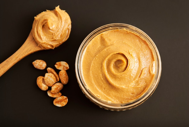 Peanuts and fresh peanut butter, black background. Premium Photo