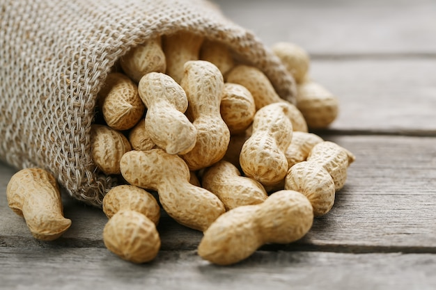 Peanuts in a miniature burlap bag on old, gray wooden surface Premium Photo