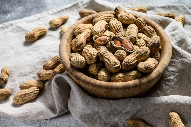 Peanuts in a shell, organic raw groundnut, top view, space for text Premium Photo