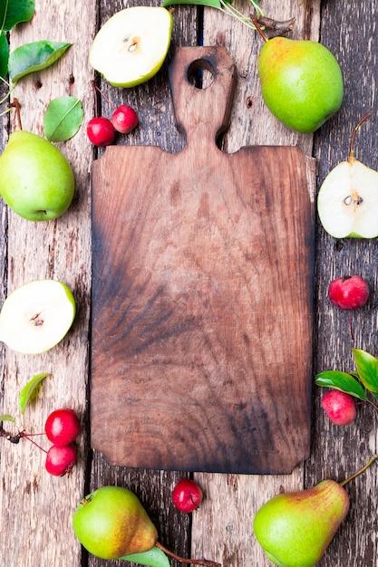 Pear and small apple around empty cutting board Premium Photo