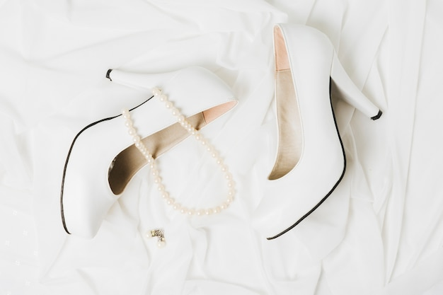 Pearl necklace and earrings with pair of wedding high heels on scarf Free Photo
