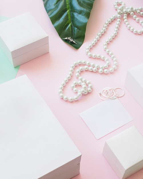 Pearls necklace and earrings with white boxes on pink background Free Photo