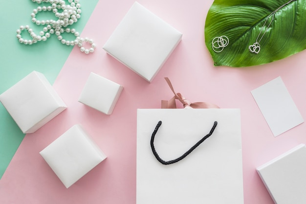 Pearls necklace and many white boxes with shopping bag on pink backdrop Free Photo
