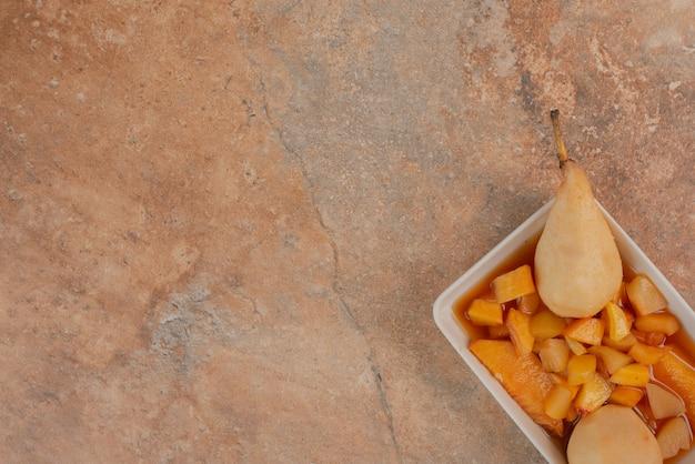 Груши и миска с фруктовым вареньем на оранжевом мраморном столе. Бесплатные Фотографии