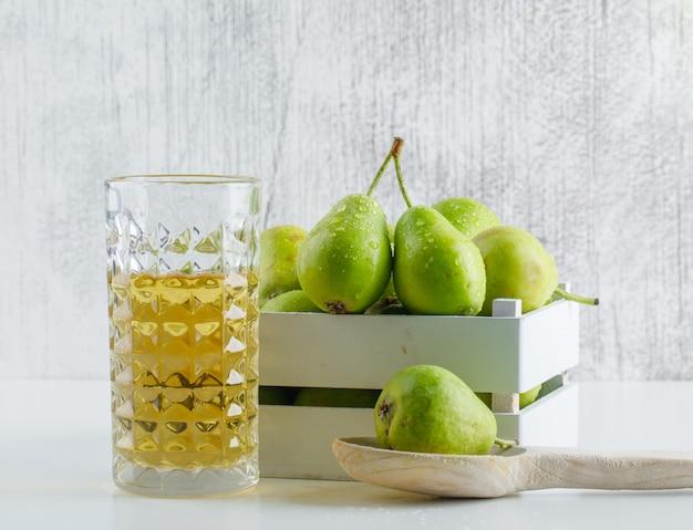木製の箱と白と汚れた壁、側面にスプーンでドリンクを飲みながら梨。 無料写真