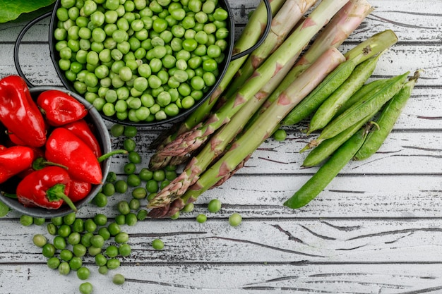 Peas in a saucepan with peppers, asparagus, green pods top view on a wooden wall Free Photo