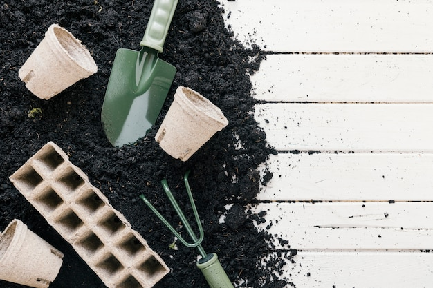Peat pot and peat tray; black soil with gardening shovel; gardening rake over wooden desk Free Photo