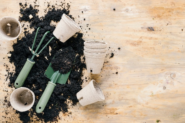 Peat pots and gardening tools with plain black soil on wooden table Free Photo