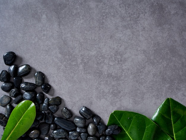 Pebbles black and leaves on gray marble background. Premium Photo