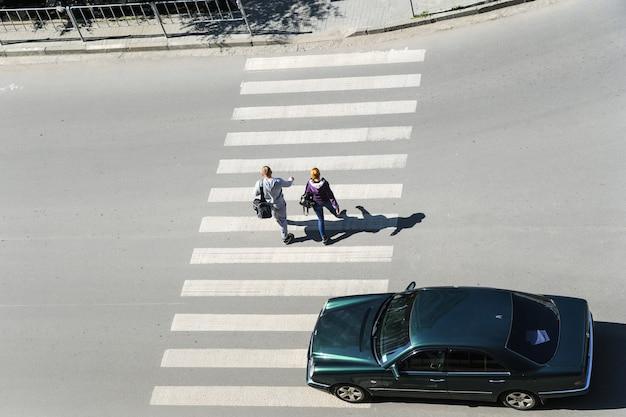 Пешеходный переход. вид сверху. ивано-франковск. украина-23.05.2017. люди переходят улицу. автомобиль идет по пешеходному переходу. Premium Фотографии