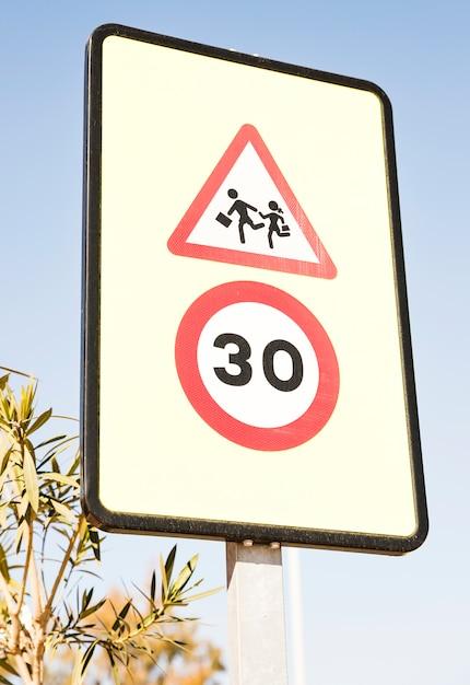 Предупреждающий знак пешеходов с 30 знак ограничения скорости против голубого неба Бесплатные Фотографии