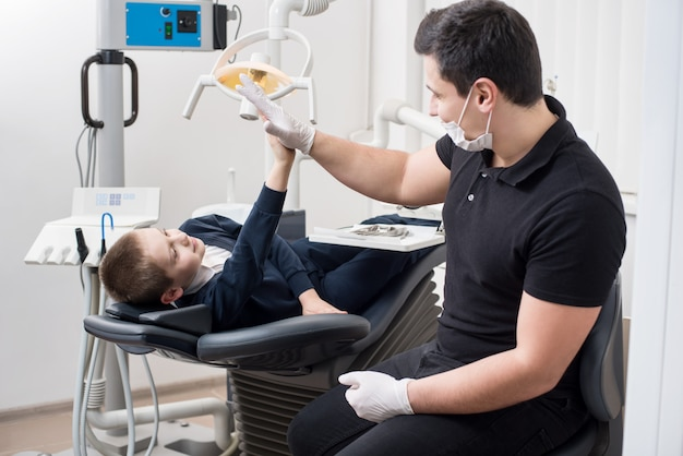 Pediatric dentist gives five young boy in dental office Premium Photo