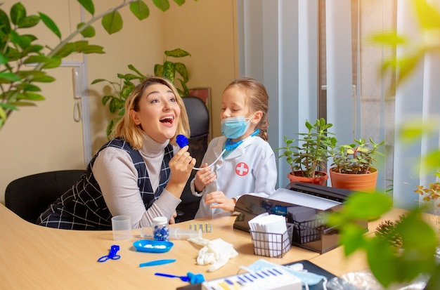 Pediatrician doctor examining a child in comfortable medical office. healthcare, childhood, medicine, protection and prevention concept. Free Photo