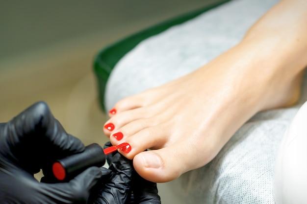 발톱에 빨간 매니큐어를 바르는 페디큐어 마스터 프리미엄 사진
