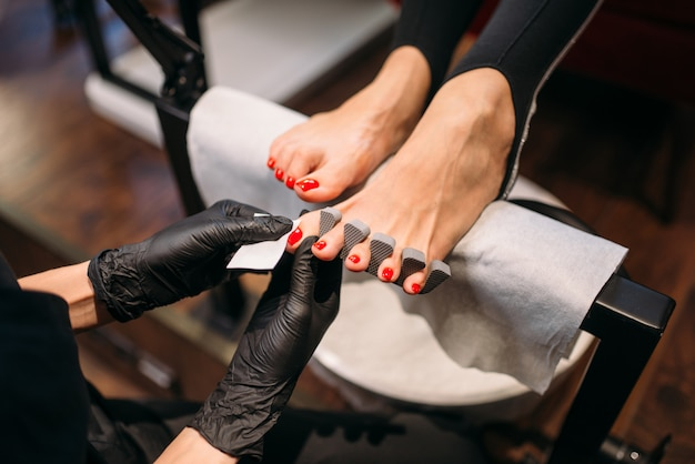 Pedicure master in gloves polishes nails with file Premium Photo