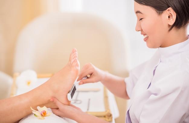 Счастливый женский pedicurist работая на клиенте на курорте. Premium Фотографии