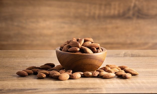 Peeled almonds wood bowl on wooden Premium Photo